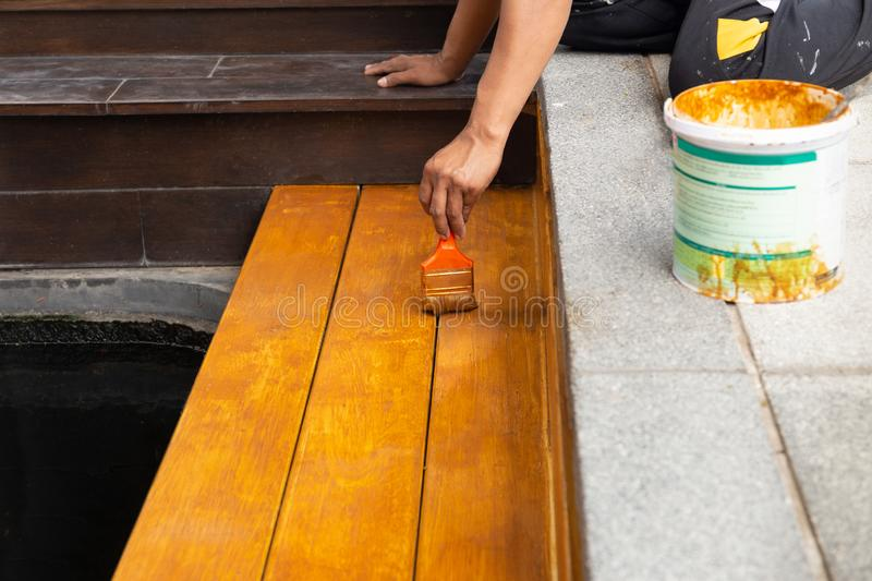 Worker varnishing lacquer on wooden floor outdoors by paint brush. Worker varnishing lacquer on wooden floor outdoors by paint brush royalty free stock images