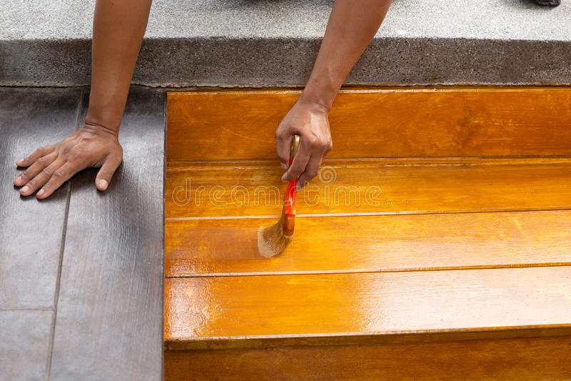 Worker varnishing lacquer on wooden floor outdoors by paint brush. Worker varnishing lacquer on wooden floor outdoors by paint brush stock photography