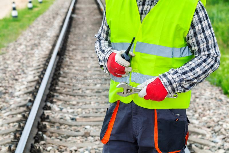 Worker with walkie talkie and wrench on railway. In summer day stock images