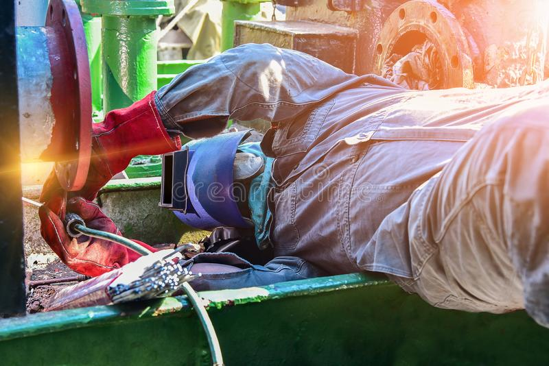 Welding ship repair. Worker ware protection mask welding conduit pipe welding on ship oil tanker under ship repair in shipyard royalty free stock image