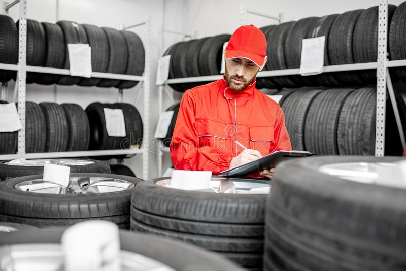 Worker in the warehouse with car tires stock image
