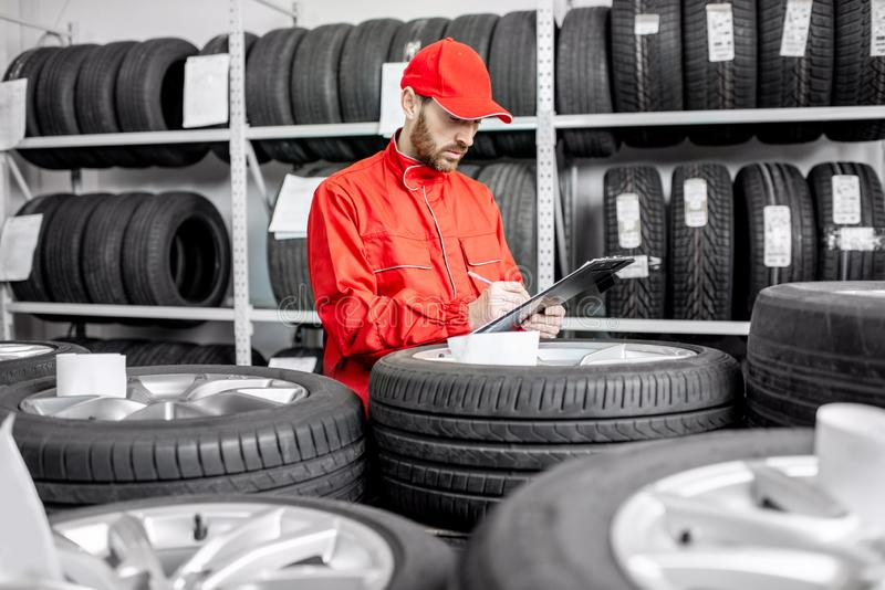 Worker in the warehouse with car tires stock photos
