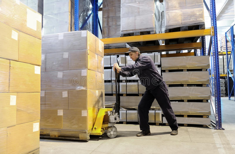 Worker at warehouse with loader stock photo