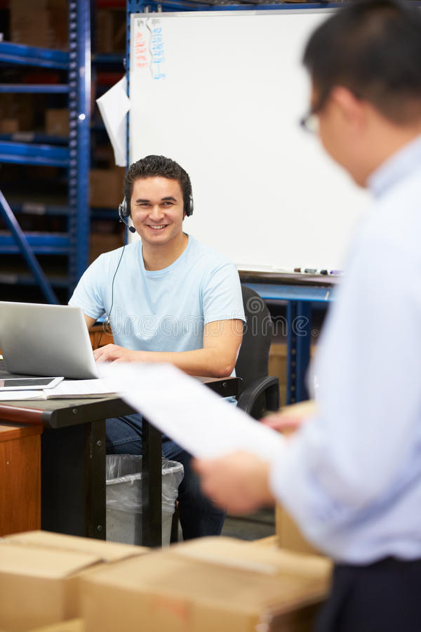 Worker In Warehouse Wearing Headset And Using Laptop stock images