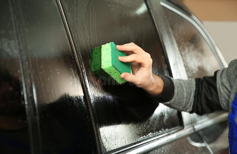 Worker washing tinted car window in shop. Closeup stock photos
