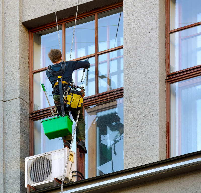 Worker washing windows of the building royalty free stock photography