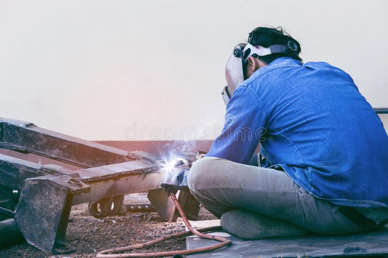 Worker welder working welding steel in industry with safety mask safety gloves and safety equipment. Wolker welding concept stock photo