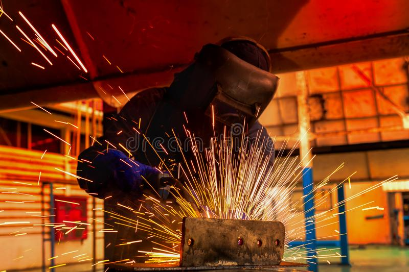 Worker is welding automotive part in car factory stock image