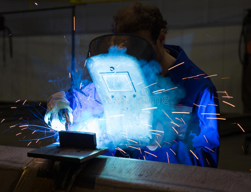Worker with welding helmet welds steel stock photo