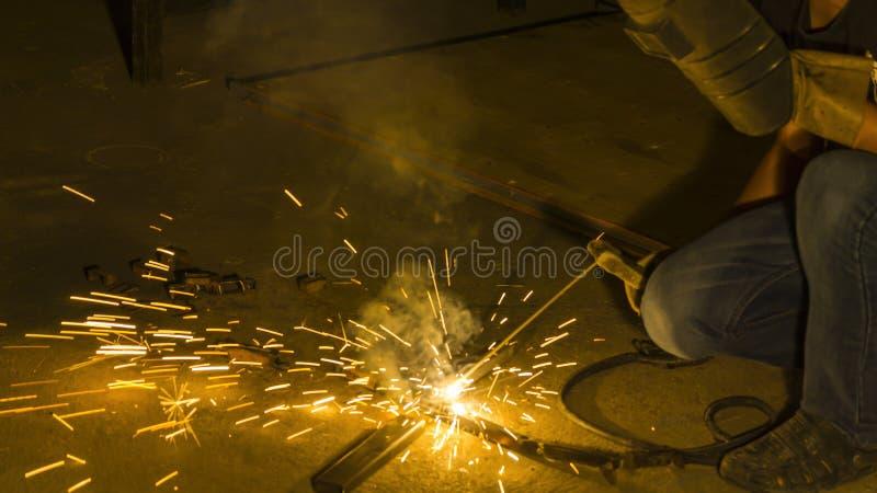 Worker welding metal, focus on flash light line of sharp spark,in low light. The worker welding metal, focus on flash light line of sharp spark,in low light royalty free stock image