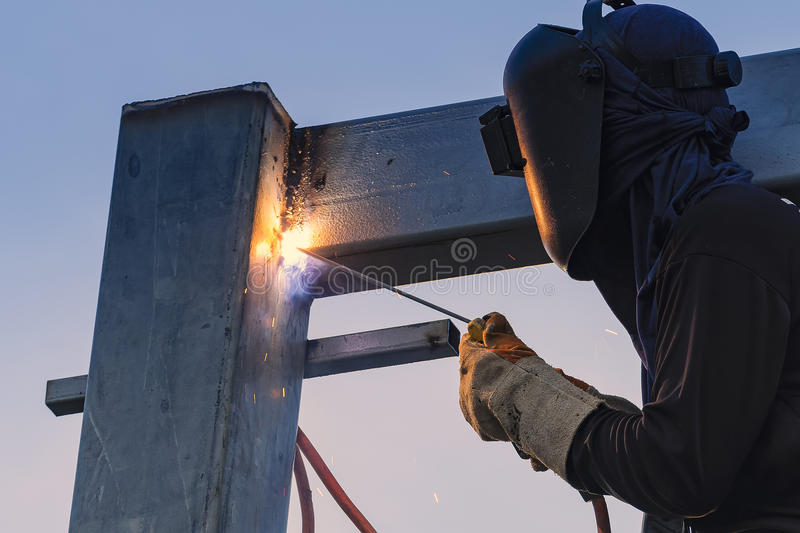 Worker welding parts of stell construction. Worker welding a parts of stell construction royalty free stock image