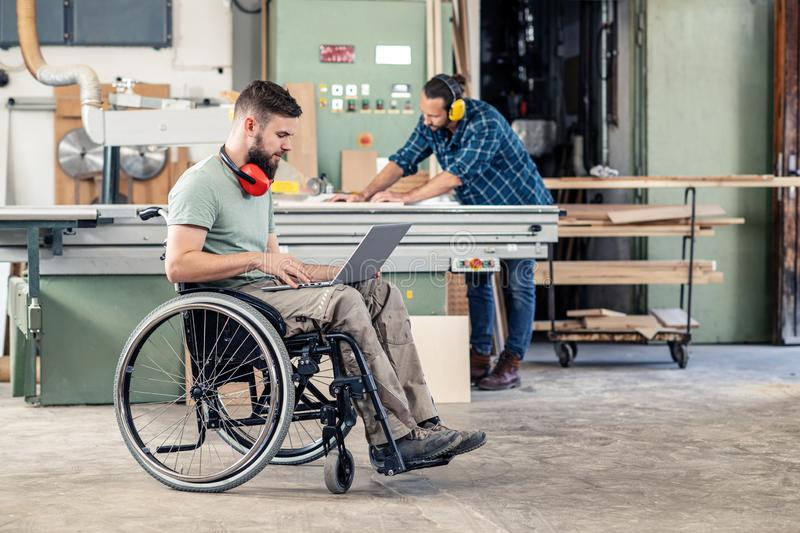 Worker in wheelchair with computer in a carpenter`s workshop with his colleagu royalty free stock images