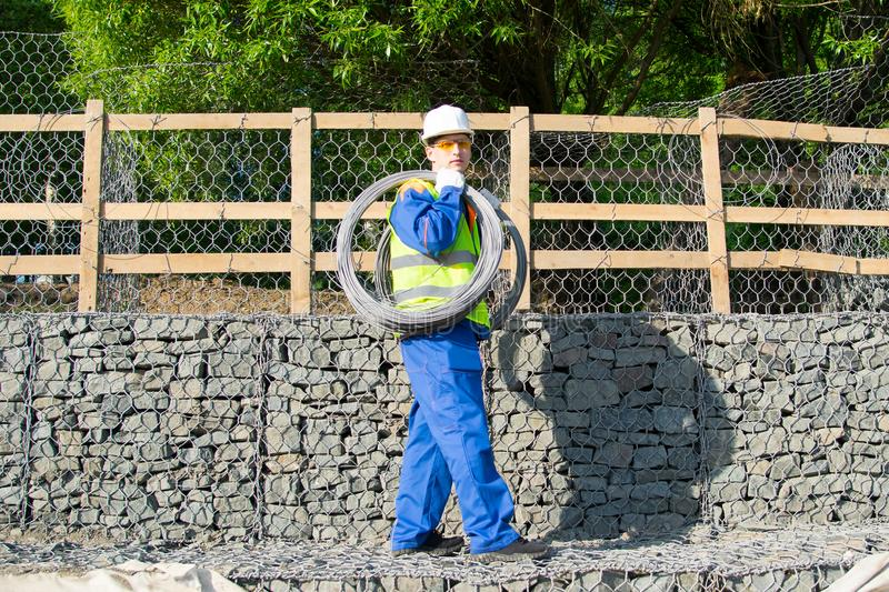A worker in a white helmet, against a background of a wooden fence and building stones, carries a wire on his shoulder stock images
