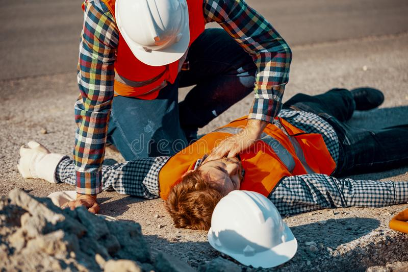 Worker in white helmet checking life functions of an injured man. Worker in white helmet checking life functions of an injured men during roadworks royalty free stock photography