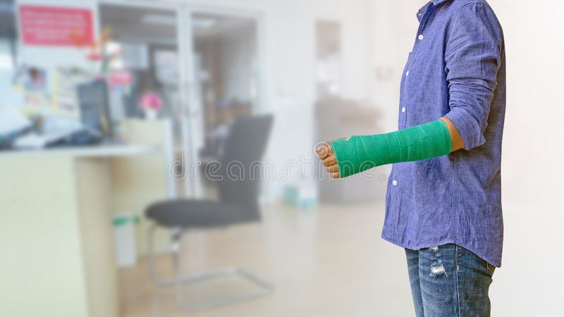 Worker woman accident on arm with green arm cast on blurred business office working space background.  royalty free stock photos