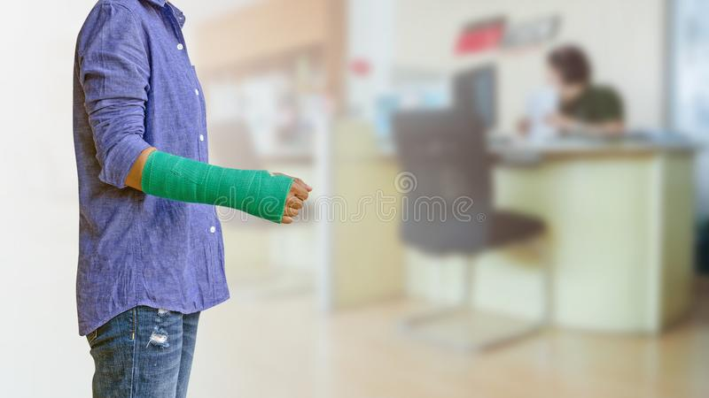 Worker woman accident on arm with green arm cast on blurred business office working space background.  stock photo