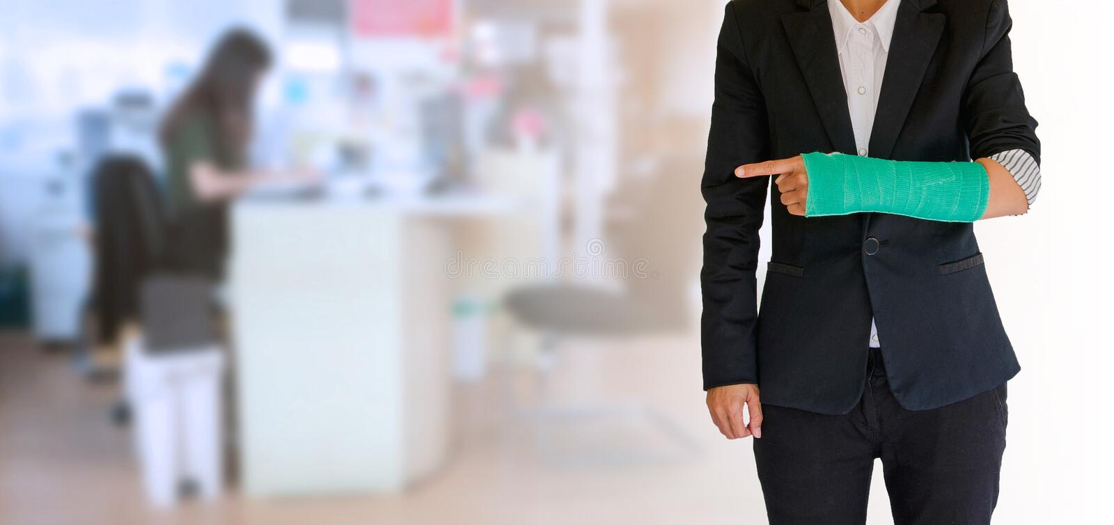 Worker woman accident on arm with green arm cast on blurred business office working space background royalty free stock photography