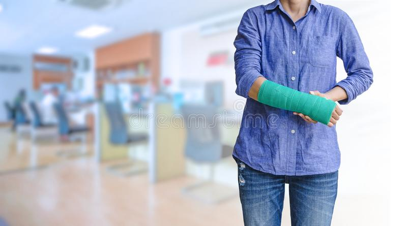 Worker woman accident on arm with green arm cast on blurred business office working space background royalty free stock photos