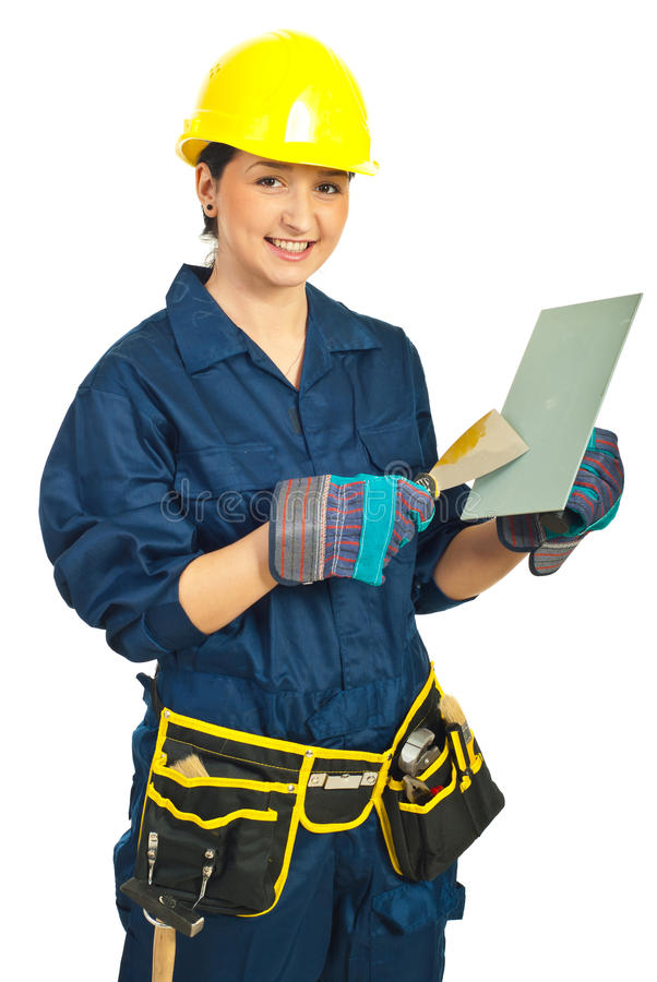 Worker woman holding notched and wall scraper. Smiling young worker woman holding notched and wall scraped isolated on white background stock image