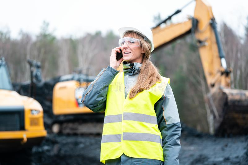 Worker woman in open-cast mining using phone royalty free stock photo