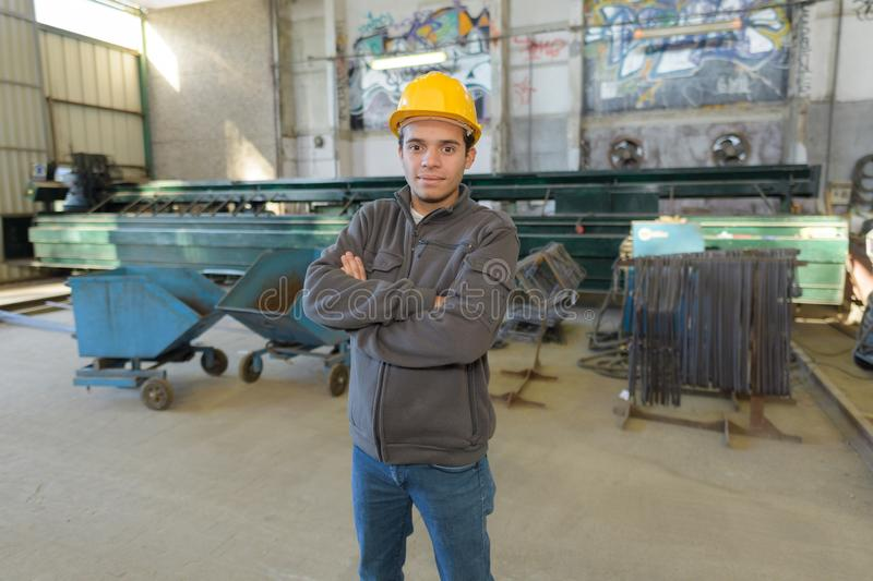 Worker in work clothes with yellow helmet in factory. Male stock images