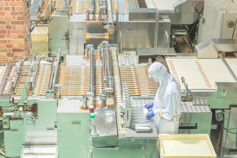 Worker working with machine in cookie factory royalty free stock photo