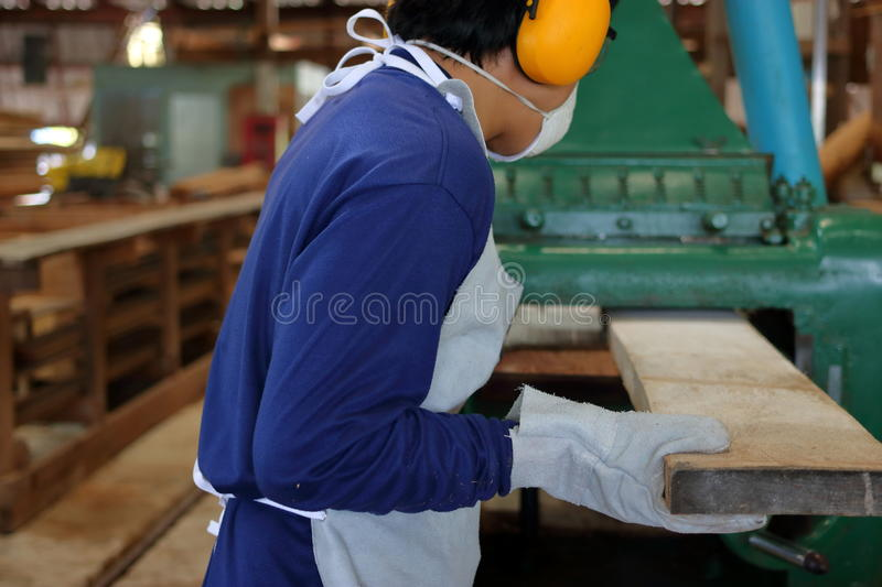 Worker is working with planing of wood machine.He is wearing safety equipment in factory. Rear view stock image