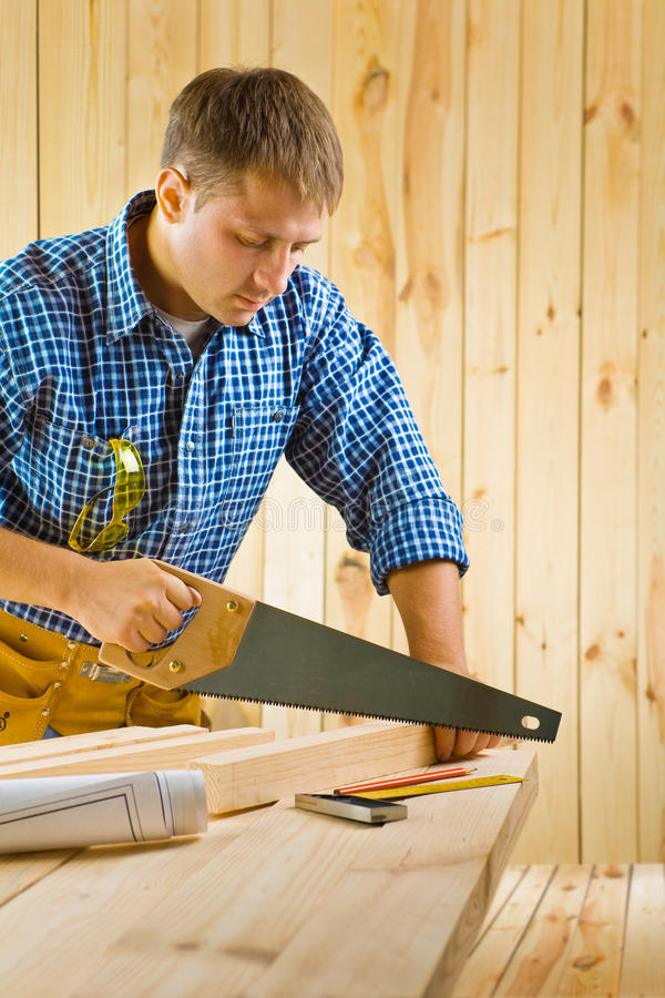 Worker works with handsaw stock photography