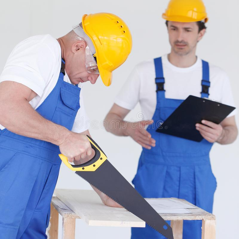 Worker works with handsaw royalty free stock photos