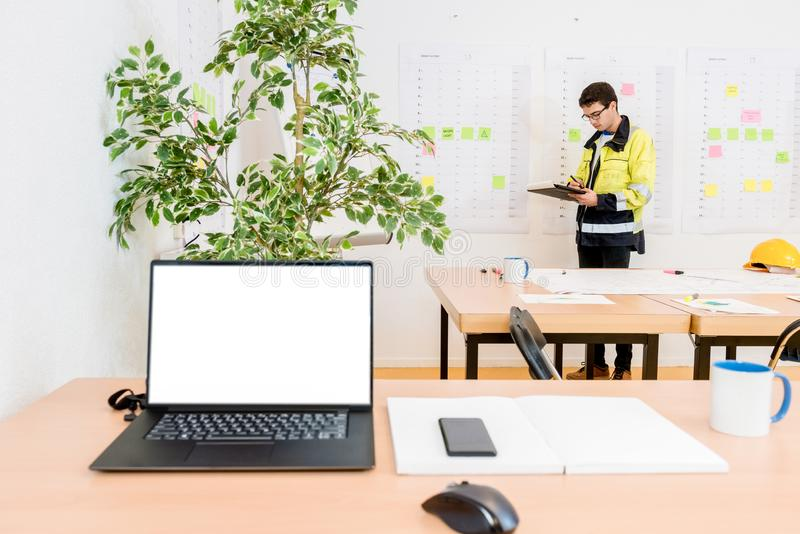 Worker Writing In Conference Room With Laptop On Foreground stock images