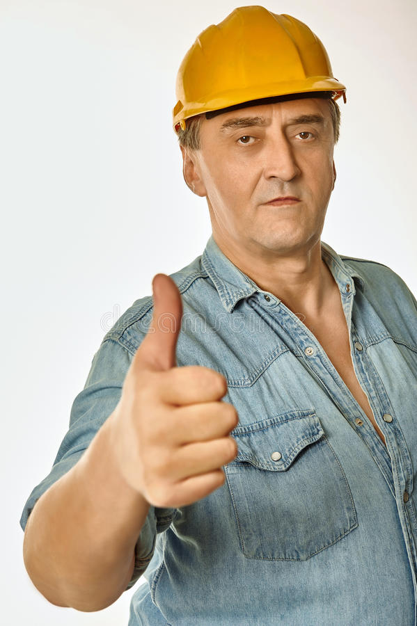 Worker in a yellow hardhat showing gesture approval stock photography