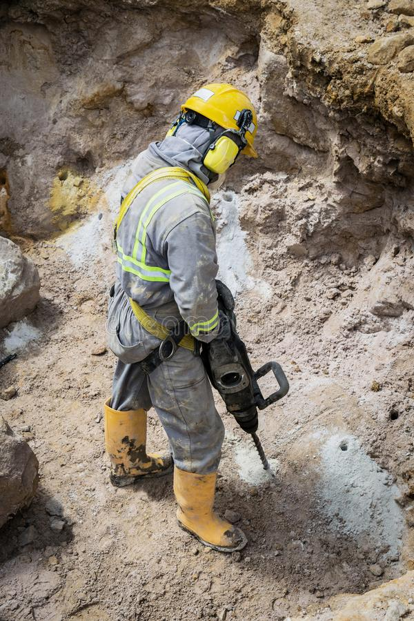 Drilling worker in action. Workerman with helmet and protective suit using drill-machine in an underground environment royalty free stock image