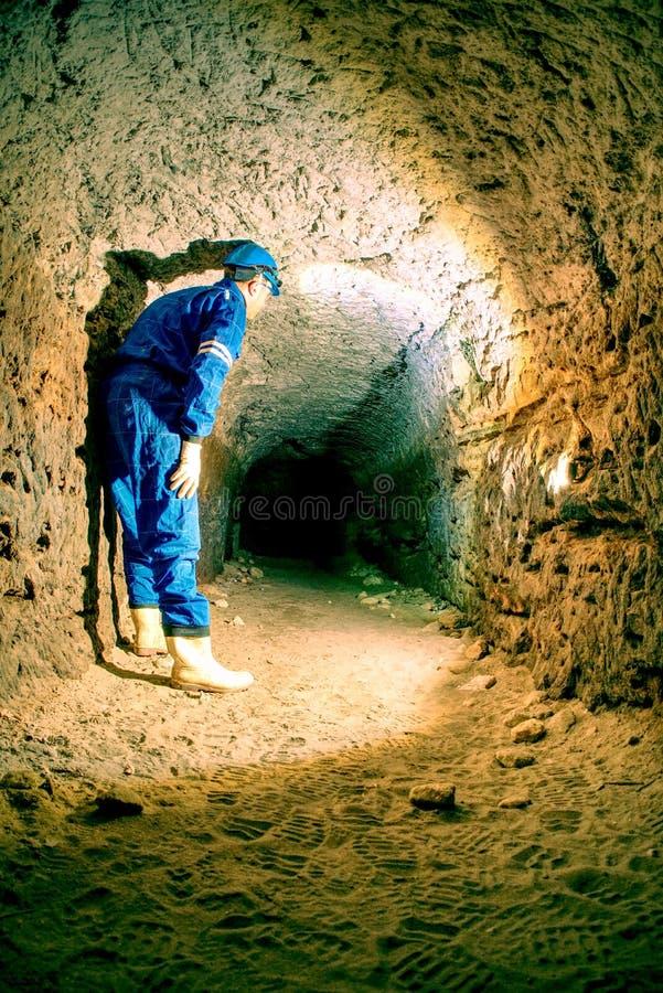 Workerman z hełmem i ochronnym kostiumem używać glowes i silną kierowniczą lampę Mężczyzna robi pracie obrazy royalty free