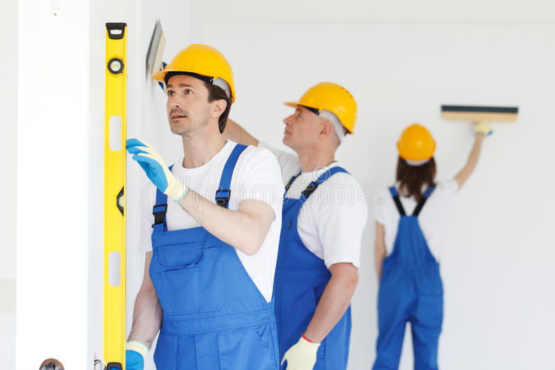 Workers align wall. Team of workers align wall at new house royalty free stock image