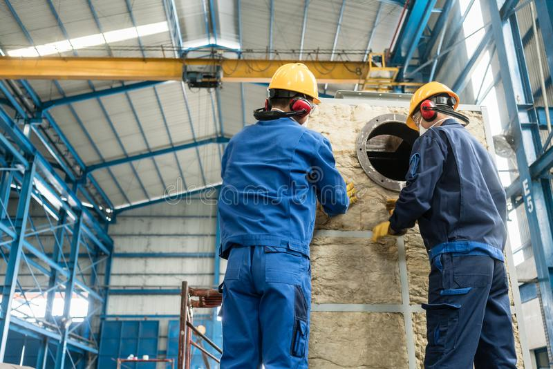 Workers applying insulation material to an industrial boiler royalty free stock photos