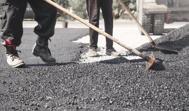 Workers arranging asphalt. Road construction. Industry stock images