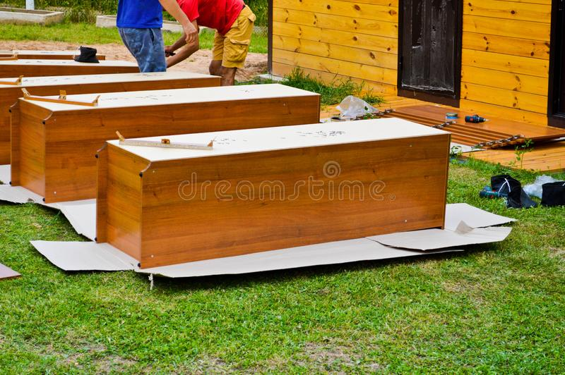 Workers assemble new wooden cabinets furniture in the street.  stock photos