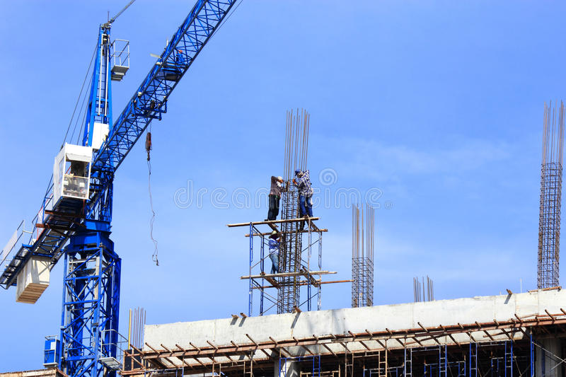 Workers binding steel bars on the construction site royalty free stock image