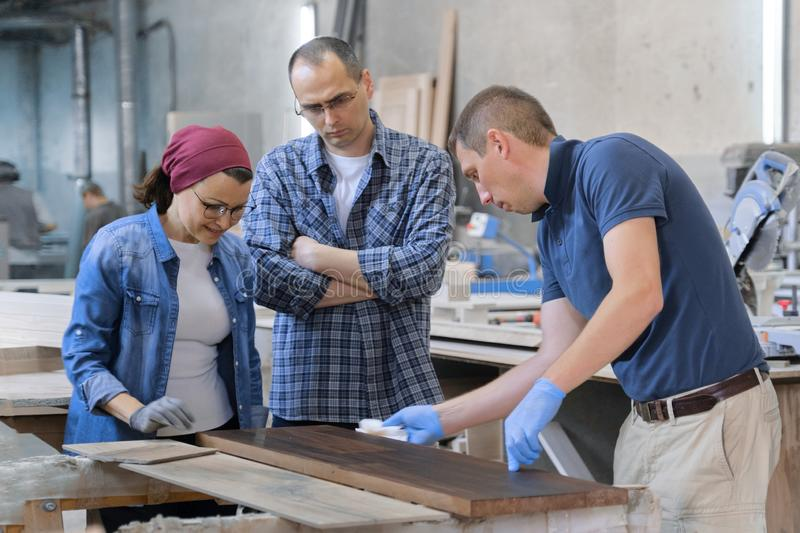 Workers in carpentry woodworking workshop, varnishing wooden plank with oil.  royalty free stock photography