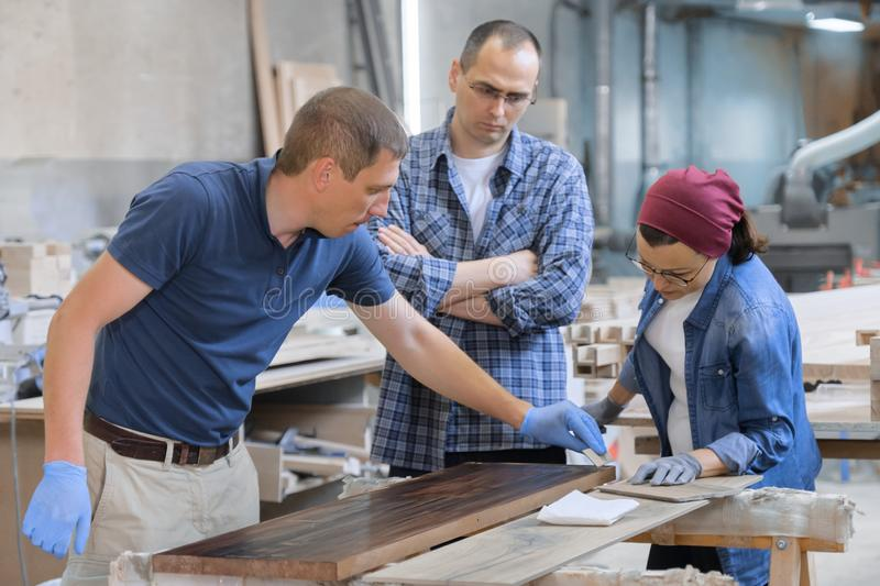 Workers in carpentry woodworking workshop, varnishing wooden plank with oil.  royalty free stock photo