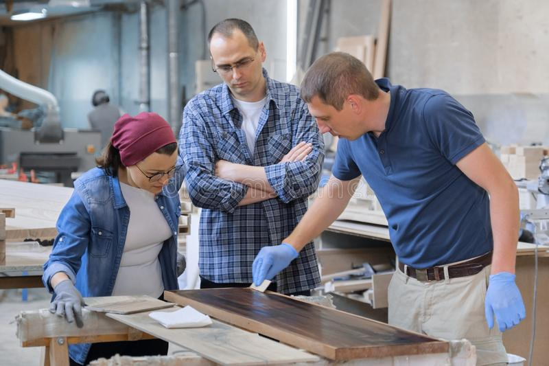 Workers in carpentry woodworking workshop, varnishing wooden plank with oil.  stock photos