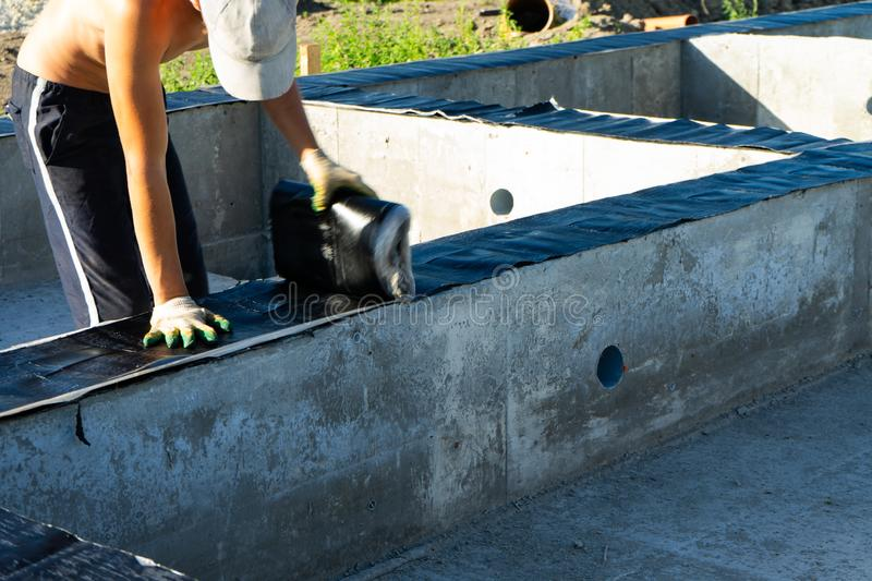 Workers carry out waterproofing of the Foundation for the construction of a wooden house. Copy paste stock photo