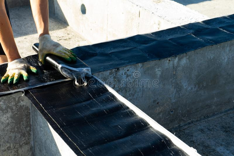 Workers carry out waterproofing of the Foundation for the construction of a wooden house. Copy paste stock photography