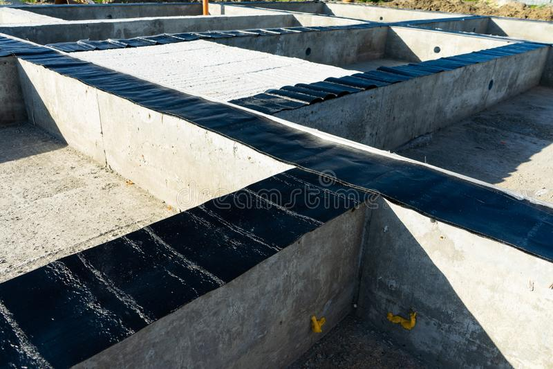 Workers carry out waterproofing of the Foundation for the construction of a wooden house. Copy paste royalty free stock image