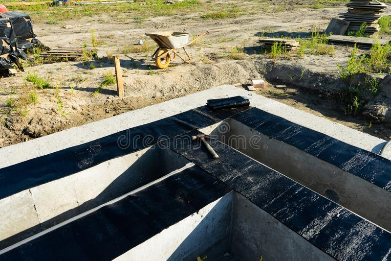 Workers carry out waterproofing of the Foundation for the construction of a wooden house. royalty free stock photos