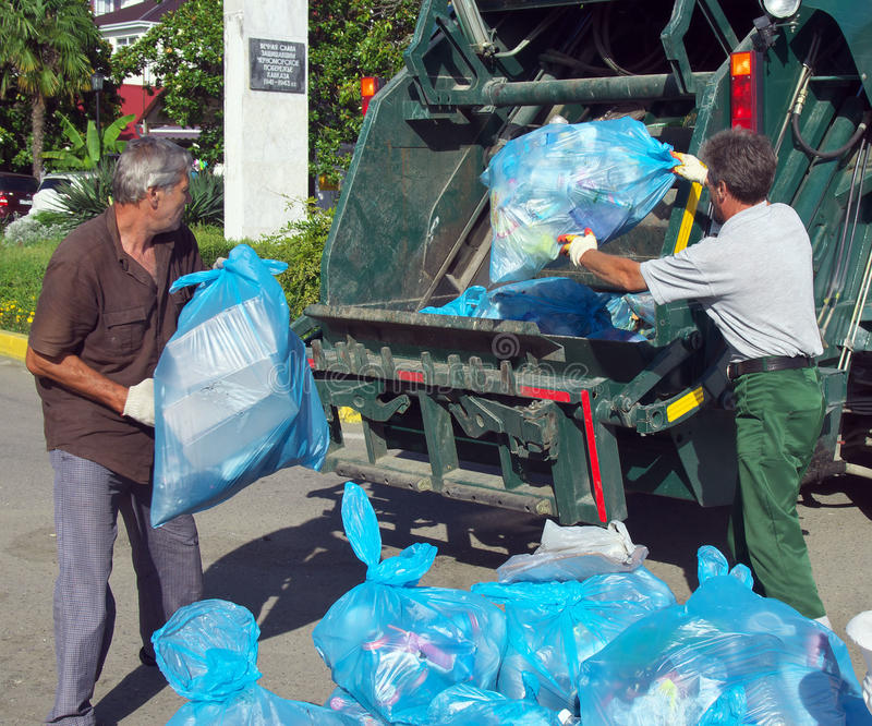 Workers charged with garbage in a garbage truck on city streets Lazarevskoye. Lazarevskoe, Sochi, Russia - June 27, 2014: Workers charged with garbage in a stock photo