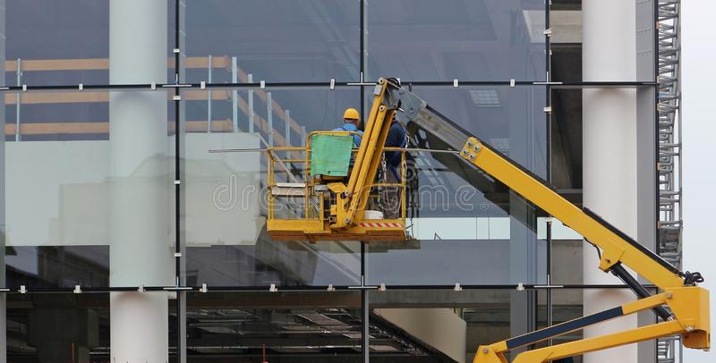 Workers on a cherry picker. They are finishing the glass facade of a building under renovation royalty free stock photography
