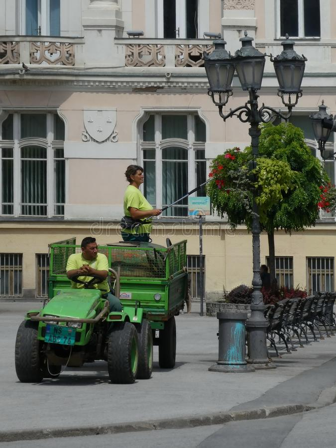 Workers from City greenery service watering flowers on the street lamp on hot day. Taking. Novi Sad, Serbia, June 25th 2019. -  Workers from City greenery royalty free stock photo