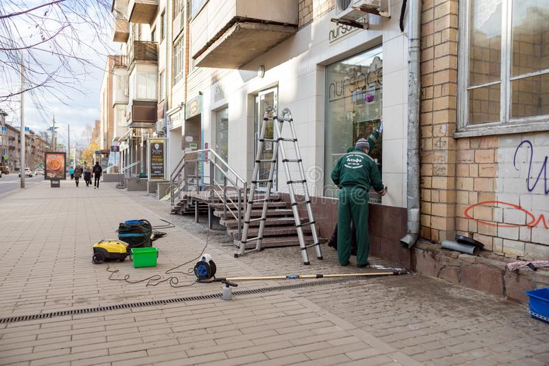 Workers of the cleaning company are engaged in washing windows and cleaning the facade after repairing an office. stock photos