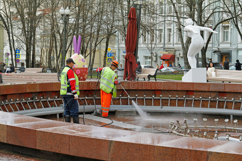 Workers cleaning a fountain with pressure washer in Novopushkinsky square royalty free stock photos